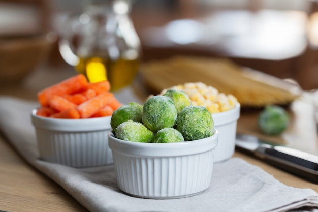 Legumes congelados, como cenoura e couve de bruxelas, nas tigelas da mesa da cozinha