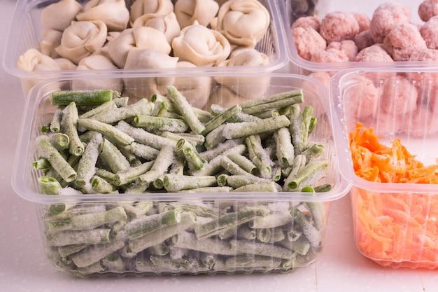 Legumes congelados e produtos de carne semiacabados em recipientes de plástico em um prato branco. almôndegas, bolinhos, feijão picado e cenoura ralada