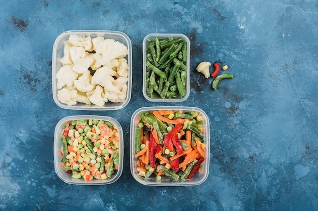 Legumes congelados: uma mistura de legumes, vagem e couve-flor em diferentes recipientes de plástico para congelar em um fundo azul.