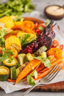 Legumes cozidos: abóbora, beterraba, cenoura, pimentão, abobrinha e milho na placa de madeira.