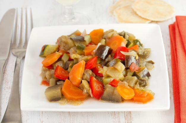 Legumes cozidos no prato e garfo com faca