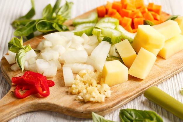 Legumes crus frescos picados para cozinhar sopa em uma placa de madeira