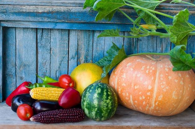 Legumes da colheita de outono: abóbora, melancia, milho, pimentão, berinjela, tomate em uma mesa de madeira