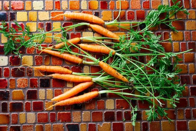 Legumes de mini cenoura em uma mesa de azulejos