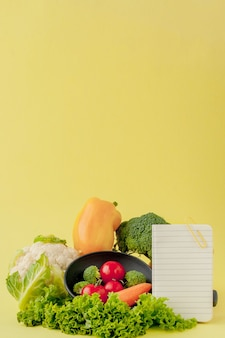 Legumes e caderno com espaço de cópia em fundo amarelo