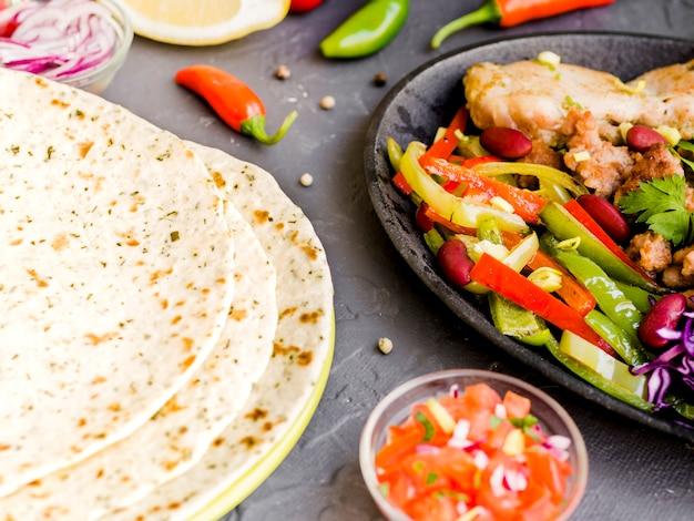 Legumes e carne ao lado de tortillas
