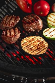 Legumes e carnes chiando na grelha com chamas, close-up