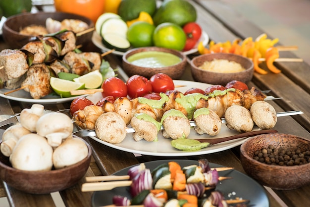 Legumes e espetos de carne com molhos
