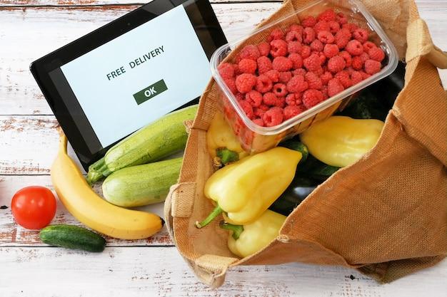 Legumes e frutas em bolsa de algodão e tablet pc, conceito de mercado online