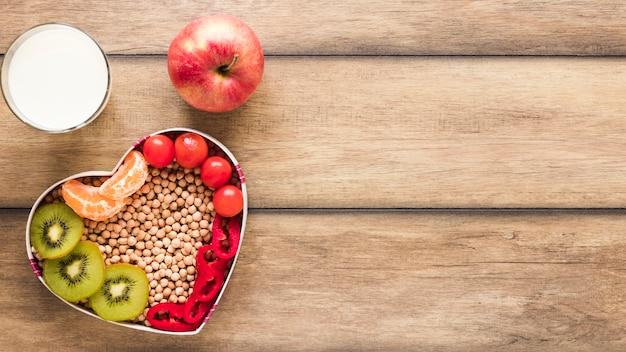 Legumes e frutas em tigela de heartshape com maçã e leite na mesa de madeira