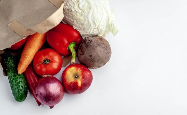 Legumes e frutas em um pacote da loja em um fundo branco