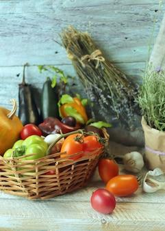 Legumes e frutas em uma cesta de ervas picantes em uma mesa de madeira conceito de colheita de outono
