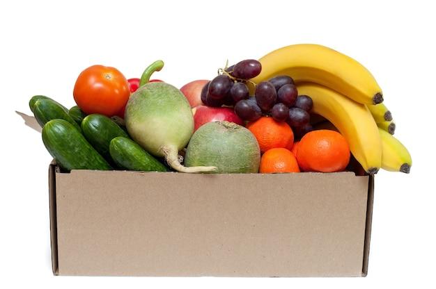 Legumes e frutas frescas em uma caixa de papelão em um fundo branco