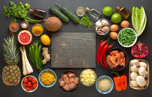 Legumes e ingredientes em torno de uma placa de madeira, vista superior