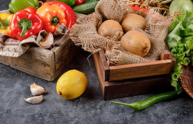 Legumes e kiwies em uma bandeja de madeira com limão e alhos ao redor.