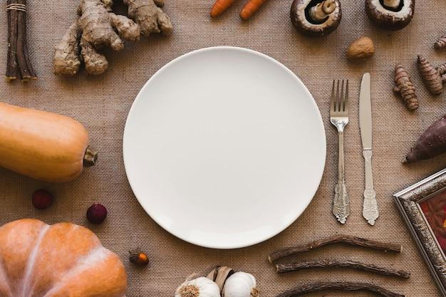 Legumes e paus em torno de prato e talheres