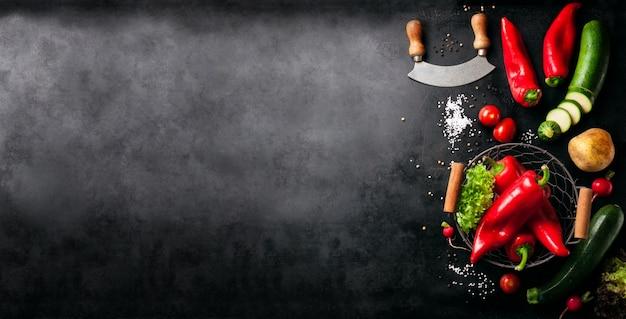 Legumes e uma faca italiano colocada à esquerda de uma tabela preta