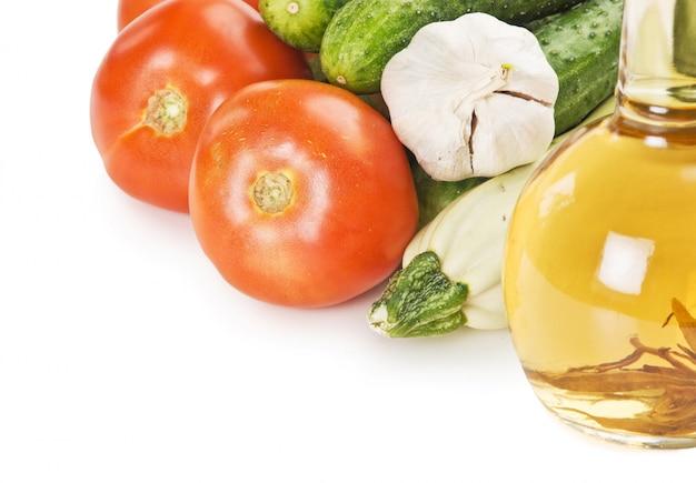 Legumes e uma garrafa de óleo, ainda vida isolada no fundo branco
