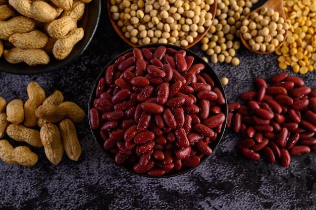 Legumes e variedade de feijões no chão de cimento preto.
