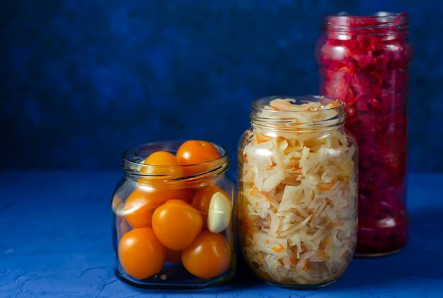 Legumes em conserva fermentados em vários frascos de vidro modernos, prontos para fechar. branco e vermelho com repolho de beterraba e tomate cereja amarelo com alho em uma parede azul clássica