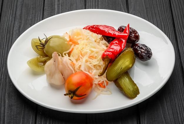 Legumes em conserva variados em um prato. em uma mesa escura