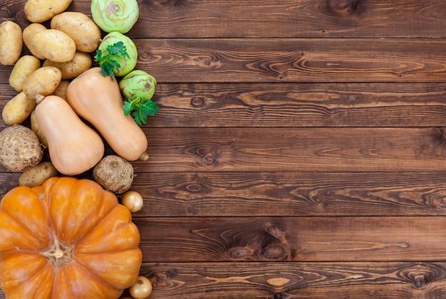Legumes em madeira. abóbora, abobrinha, batata, cebola e outros vegetais