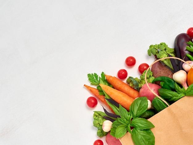 Legumes em saco de papel em fundo branco.