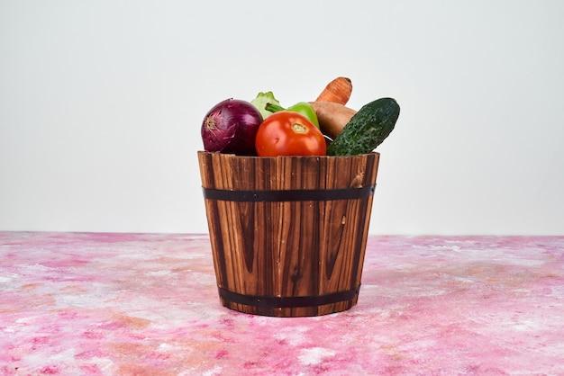 Legumes em um balde de madeira.