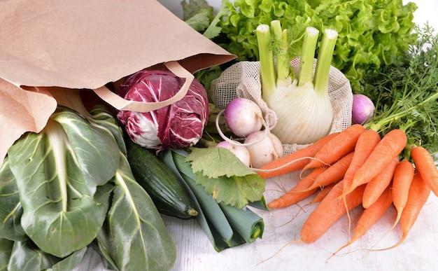 Legumes em um saco de papel reutilizável entre outros legumes frescos em uma mesa branca