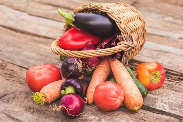 Legumes em uma cesta de vime em um fundo de madeira. culturas frescas, produtos agrícolas, uma horta em casa. copie o espaço