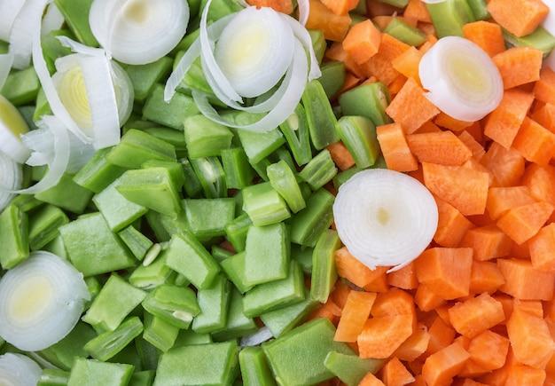 Legumes ervilhas e cenouras slicing for salad and soup. fechar-se.