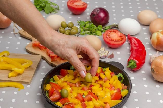 Legumes fatiados na panela. mãos colocam azeitona na panela