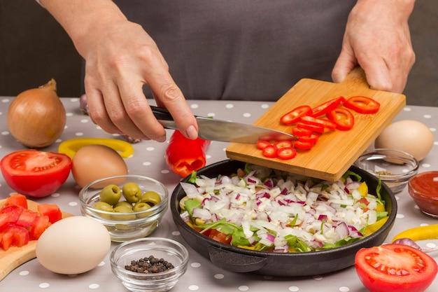 Legumes fatiados na panela. mãos colocam tomates na panela