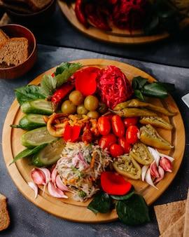 Legumes fatiados pepinos tomates pimentas verdes na mesa de madeira marrom no cinza