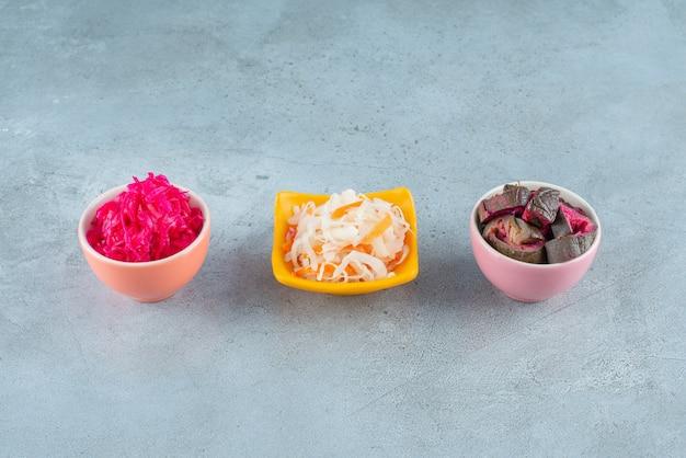 Legumes fermentados em uma tigela, na mesa de mármore.