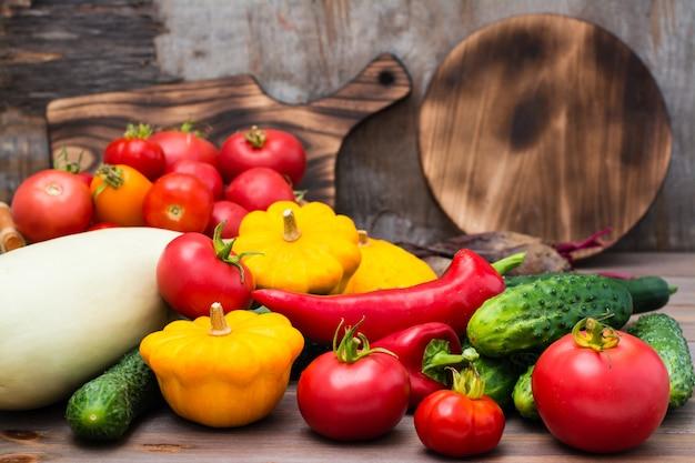 Legumes frescos - abóbora, pepino, tomate, abobrinha, pimentão em uma mesa de madeira