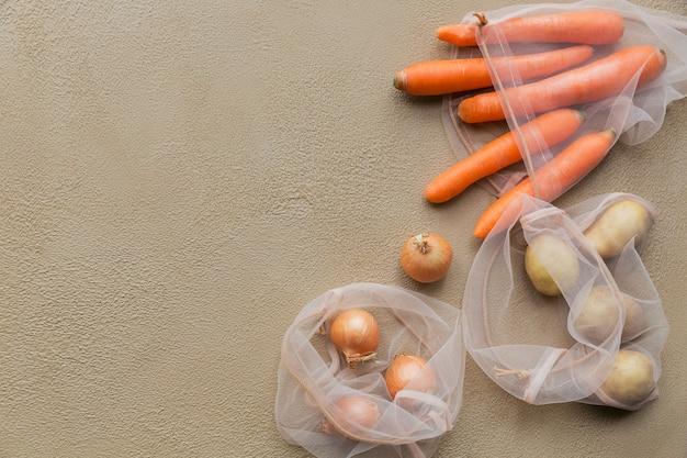 Legumes frescos, batatas, cebolas e cenouras embalados em um saco de malha reutilizável com cordão. recusa de embalagem de plástico. embalagem ecológica.