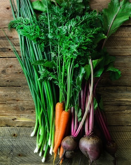 Legumes frescos - cenouras, beterrabas, cebola verde em madeira. colheita.