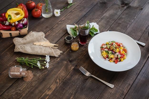 Legumes frescos coloridos em um prato branco sobre um fundo escuro de madeira