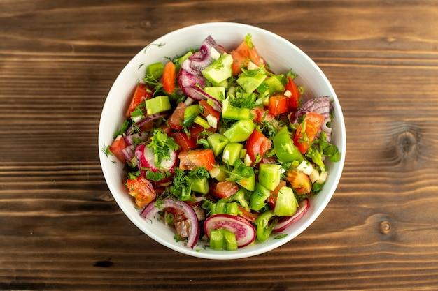 Legumes frescos coloridos fatiados, como pepino tomate vermelho cebola na superfície rústica de madeira