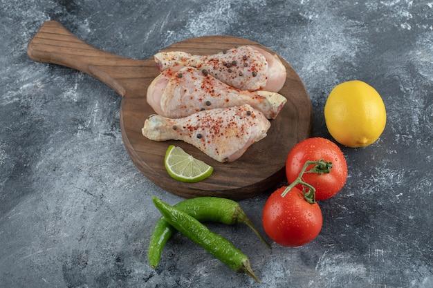 Legumes frescos com coxinhas de frango prontas para cozinhar.