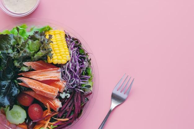 Legumes frescos com molho para salada e garfo no fundo rosa