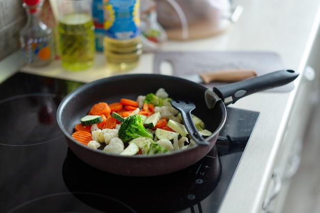 Legumes frescos cozinhando na panela na cozinha de casa. fechar-se.