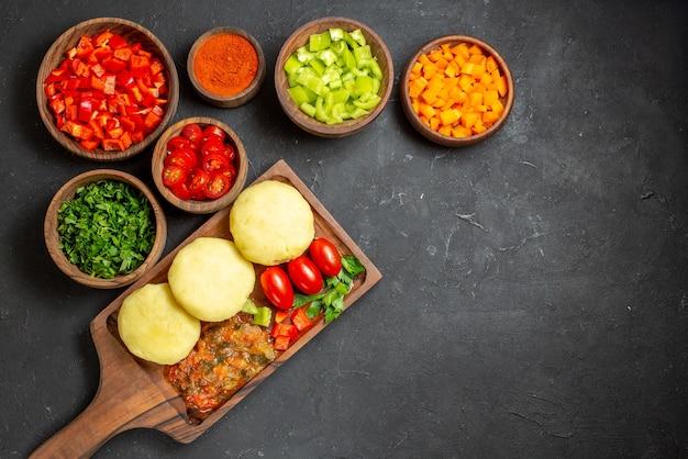 Legumes frescos e alimentos picados com verduras e pimenta na mesa preta