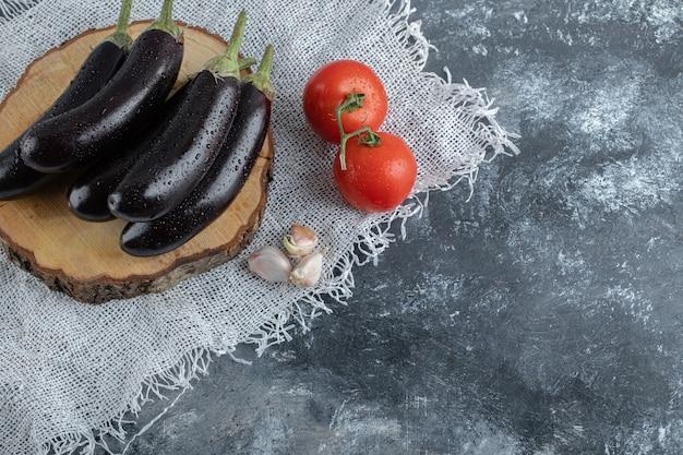 Legumes frescos e crus. berinjelas roxas na placa de madeira e tomate.