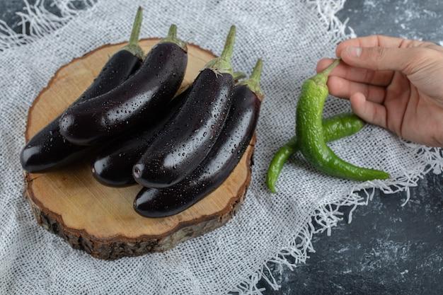 Legumes frescos e crus. pilha de berinjela e pimenta verde segurando com a mão.
