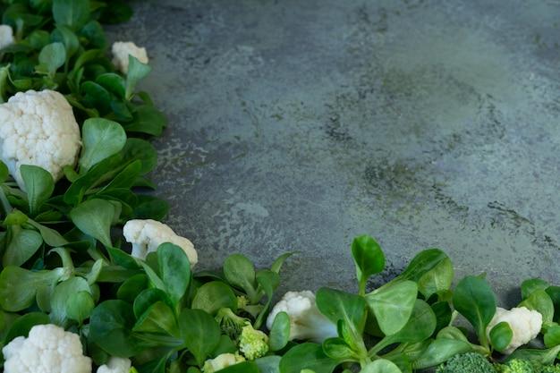 Legumes frescos e folhas de salada de milho no fundo à moda antiga
