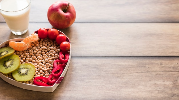 Legumes frescos e frutas com copo de leite em fundo de madeira