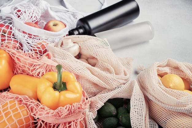 Legumes frescos e frutas em sacos ecológicos, garrafas de água reutilizáveis
