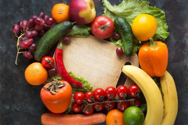 Legumes frescos e frutas em um fundo preto. vitaminas e minerais. vista do topo. abra espaço para o seu texto.